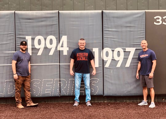 Former Auburn players Chris Morrison (left), Rob Macrory (center) and Tim Hudson (right) pose in front of the years they represented the Tigers at the College World Series on June 12, 2019, at Plainsman Park in Auburn.