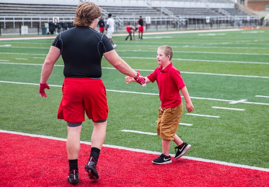 Danny Lynch high-fives a Ball State football player at Scheumann Stadium.