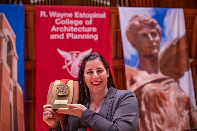 R. Wayne Estopinal's daughter, Ashley, displays a president's award honoring his contributions to Ball State.