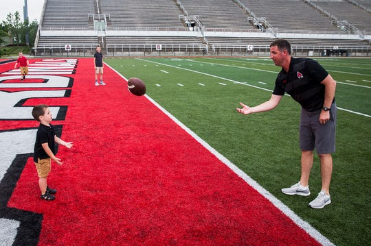 Joey Lynch tosses a football with his children at Scheumann Stadium.