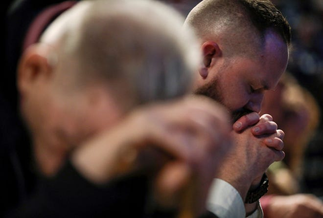 Joel Miller, a missions and outreach pastor, prays on the second day of the Southern Baptist Convention's annual meeting on Wednesday, June 12, 2019, in Birmingham, Ala.  The president of the Southern Baptist Convention has apologized for the sexual abuse crisis besetting his denomination and outlined an array of steps to address it.  ( Jon Shapley/Houston Chronicle via AP)