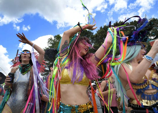 Fans participate in the Mardi Gras Parade on Thursday during the Bonnaroo Music and Arts Festival in Manchester, Tenn.