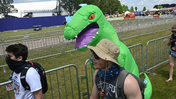 Fans and a T-Rex enter the festival on Thursday during the Bonnaroo Music and Arts Festival in Manchester, Tenn.