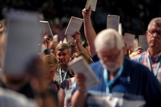 Bill Golden, and thousands of others, hold up copies of a training handbook related to sexual abuse within Southern Baptist churches during a speech by SBC President J. D. Greear on the second day of the SBC's annual meeting on Wednesday, June 12, 2019, in Birmingham, Ala.  Greear has apologized for the sexual abuse crisis besetting his denomination and outlined an array of steps to address it. ( Jon Shapley/Houston Chronicle via AP)