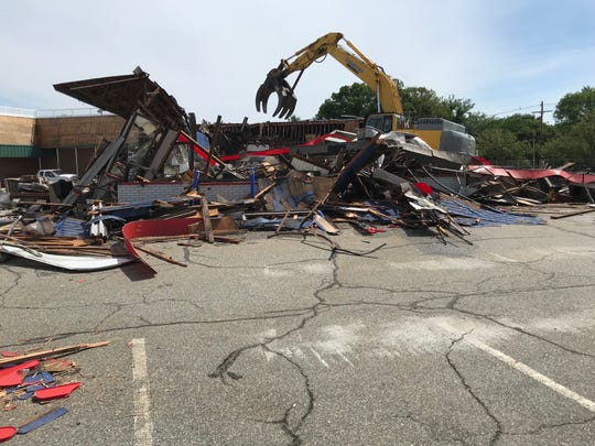 It wasn't a wrecking ball but an excavator that took down Butler's long-time Burger King building on Wednesday.