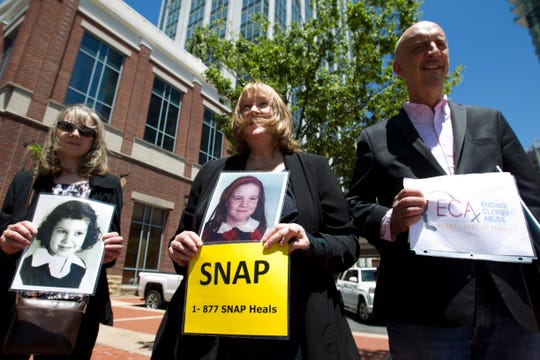 Becky Ianni, center, a victim of priest abuse, holds a picture of her younger self along with other demonstrators outside the venue where the United States Conference of Catholic Bishops 2019 Spring meetings are being held in Baltimore, Tuesday, June 11, 2019.  Ianni says she was 8-years-old when the priest of her family parish began to abuse her.