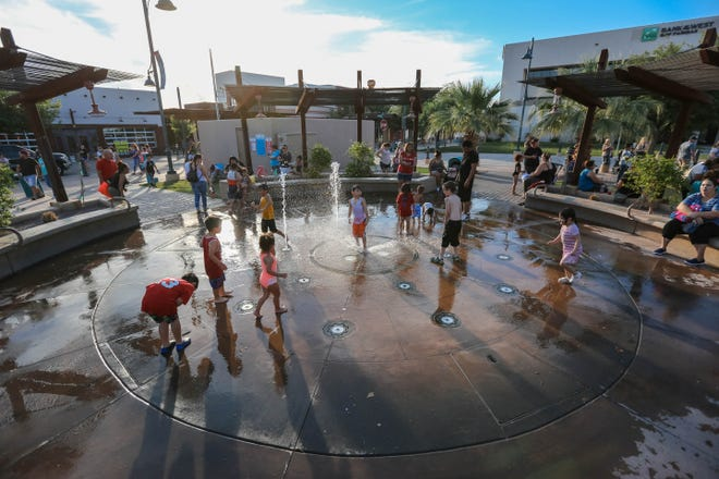 Children play in a splash pad at the evening farmers market presented by the Farmers and Crafts Market of Las Cruces in Downtown Las Cruces on Wednesday, June 12, 2019.