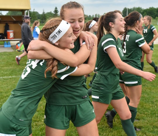 Avery Fenchel, who scored Novi's two goals of regulation, hugs a teammate after the Wildcats defeated Forest Hills Central to advance to the Div. 1 state finals.