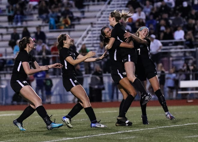 Plymouth soccer players rejoice after their victory-clinching penalty kick.