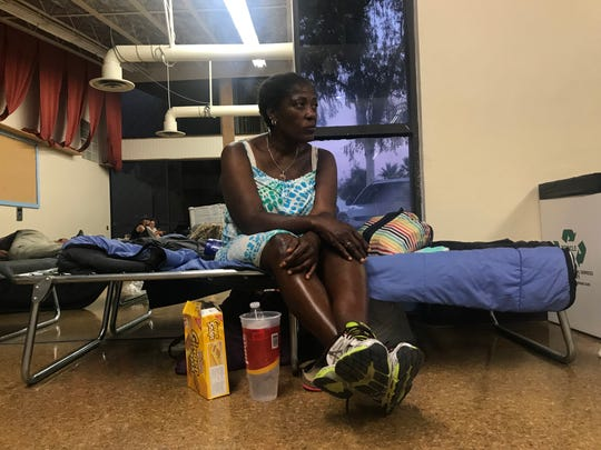 Lachelle Smith rests on her cot while Riverside County staffers prepare to pass out pizza to those staying the night at Demuth Park Community Center on  Tuesday, June 12, 2019.