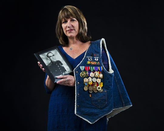 Karina bland holds a photo and medals of her veteran father, Marine Captain David John Bland, a decorated Vietnam War veteran who retired in 1979 after 21 years of service.
