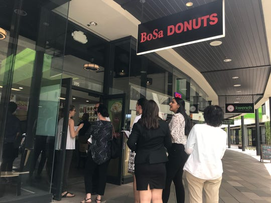 A line of people stand outside the new Bosa Donuts location in the Arizona Center on June 13.
