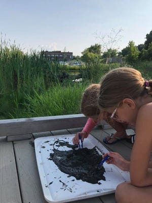 Khloe and Kayla Faust search for macroinvertebrates at an event at Wetlands County Park in 2018.