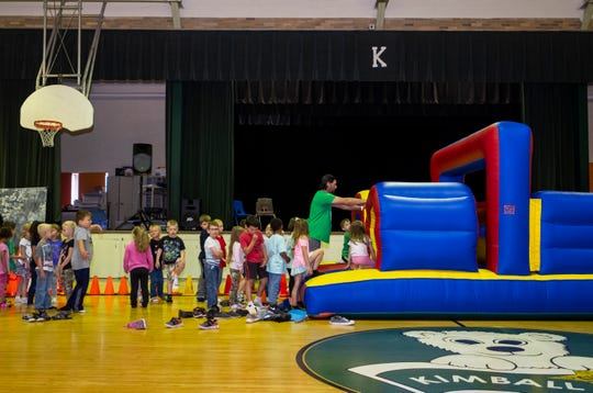 Kids line up for a run through an inflatable bounce house on the last day of school Thursday, June 13, 2019 at Kimball Elementary.