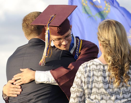 Salutatorian Jason Logan receives a hug from his dad, Tim, as his mom, Julie, looks on.
