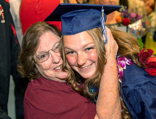 Morgan Osborn gets a hug from her grandmother Mimi Johnson after completing graduation ceremonies.
