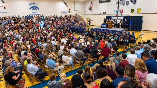 A capacity crowd attends the graduation ceremonies in the high school gymnasium.