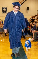 Robert Gschwind attends graduation ceremonies with his dog, Lucky.