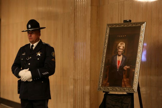 A member of the Oregon State Police Honor Guard stands by a photo of the late Sen. Jackie Winters during a celebration of her life at the Oregon State Capitol in Salem on June 13, 2019.