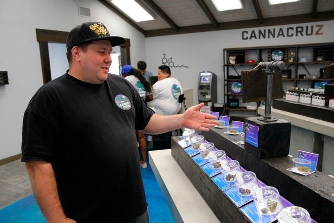 Grant Palmer shows the cannabis flower available for sale June 12, 2019, at CannaCruz, Salinas' newest dispensary that opened over the previous weekend.