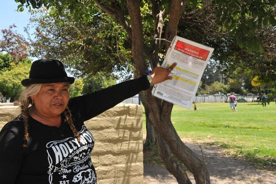 Rita Acosta recently moved back to Sherwood Park in Salinas after living with family. She points to an announced cleanup for June 14, 2019.