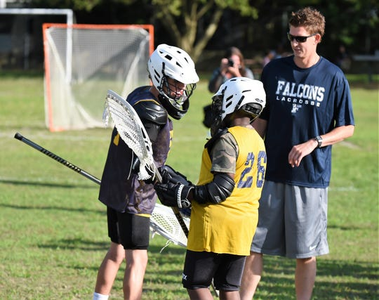 The goalies of the Doverdale Hawks and Fruitland Falcons shake hands before the first-ever home lacrosse game at the Doverdale Playground on Wednesday, Jun. 12, 2019.