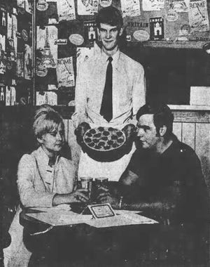 In the photo waiter Mark Lewis serves a pizza to Carolyn Mueller and Chris Gerry in 1968. Mark seems awfully pleased, while his customers remain irritated.