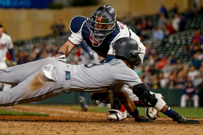 Seattle Mariners' Dee Gordon scores past Minnesota Twins catcher Mitch Garver during the 10th inning of a baseball game Wednesday, June 12, 2019, in Minneapolis. The Mariners won 9-6 in 10 innings. (AP Photo/Bruce Kluckhohn)
