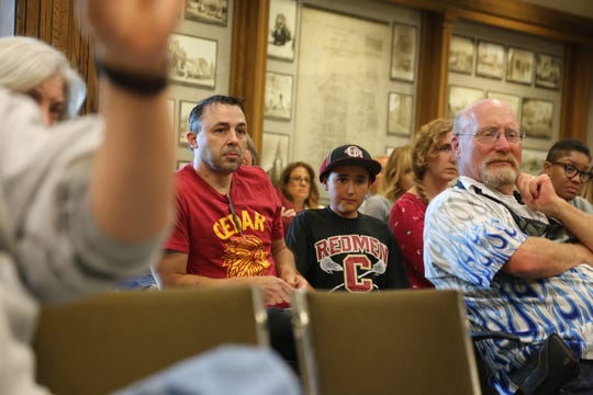 """Supporters of a proposal to turn a Cedar City water tank with artwork of the former Cedar High mascot, the """"Redman,"""" hold signs at Wednesday's city council meeting."""