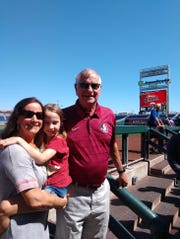 Mary Beth (Martin) Buchanan with daughter Lexi and father Mike Martin on the dugout steps at TD Ameritrade Park in Omaha, Nebraska, Wednesday.