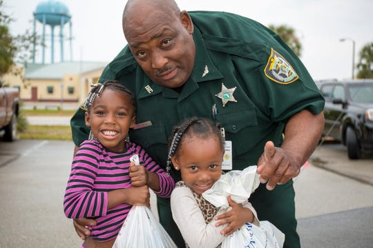 Sherriff's Deputy Teddy Floyd with two girls who received a bag of books at the Book Em event in 2016.
