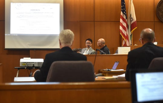 Huy Fong Foods CEO David Tran, on the right of the witness stand, sits with interpreter Michael Hong on Thursday in the civil trial between the company that makes Sriracha sauce and Camarillo grower Underwood Ranches.
