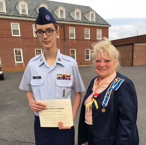 Cadet/MSgt Jacob M. Currey, a member of the Cumberland Composite Squadron/ Civil Air Patrol Cadet Program, receives a certificate from Sarah Tarpine, Regent, Greenwich Tea Burning Chapter of the National Society Daughters of the American Revolution.