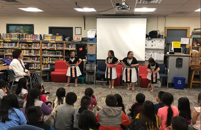 Mary Jo Lechner, left, watches a Hmong dance performed by students in May at Rothschild Elementary School in honor of Lechner's retirement.