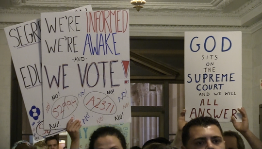 Anti-vaccination protesters hold signs outside an Assembly Health Committee meeting at the state Capitol in Albany; June 13, 2019.