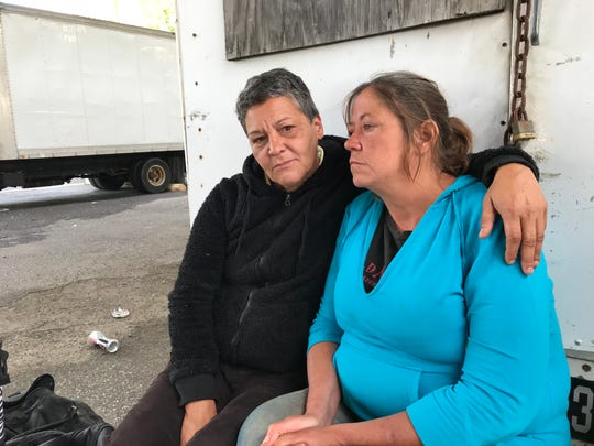 Ingrid VonFricken (left) and Hope Buchanan sit on a truck bumper underneath an I-95 overpass where they have been living. Buchanan's boyfriend began seizing up earlier in the day and had to be hospitalized by paramedics, but the friends said they feel invisible because they're homeless.
