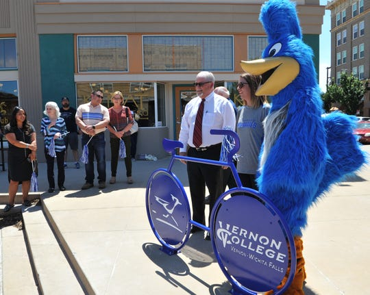 Vernon College, president Dusty Johnston, left and Downtown Wichita Falls Development director Jana Schmader, with the help of the Vernon College mascot, unveiled the Vernon College sculptured bicycle rack at the corner of 8th at Ohio Street, Thursday afternoon.