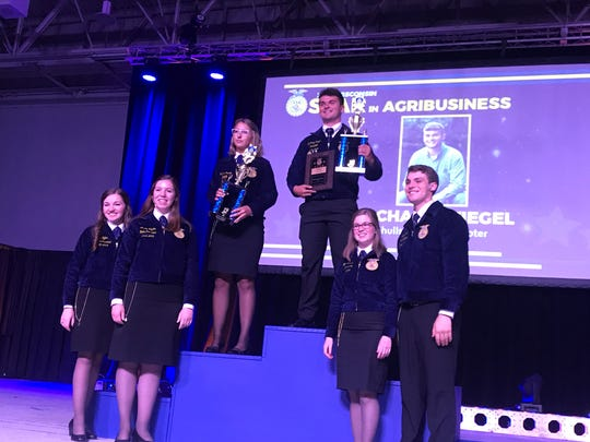 Zach Wiegel (center) of the Schullsburg FFA Chapter was named the 2019 Wisconsin Star in AgriBusiness. He is joined by runner-up Katrina Pokorny of the Waupun FFA Chapter.
