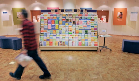 This file photo shows an unidentified worker walking past a display of a new line of cards at Hallmark Cards Inc. in Kansas City, Kan.