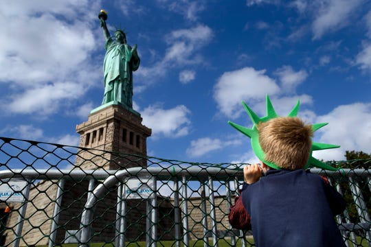 A child looks up at the Statue of Liberty in New York City.