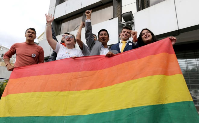 Efrain Soria, center, celebrates with other leaders of the gay community after the legalization of same-sex marriage, outside the court in Quito, Ecuador, Wednesday, June 12, 2019.