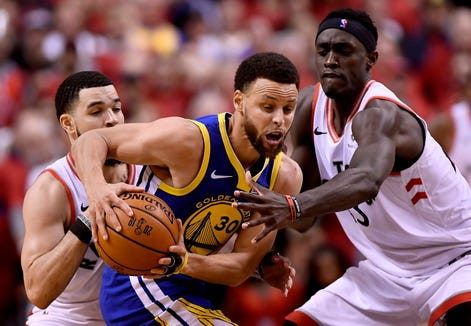 Golden State Warriors guard Stephen Curry (center) tries to fend off Toronto Raptors guard Fred Van Vleet (left) and Pascal Siakam (right) during the second half of Game 2 of the NBA Final.