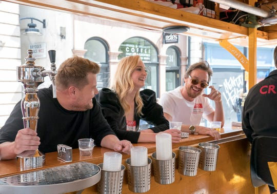 'The Late Late Show' host James Corden, left, enjoys a libation break with actors Sophie Turner and James McAvoy during a double-decker bus tour on the CBS late-night program's latest London visit.