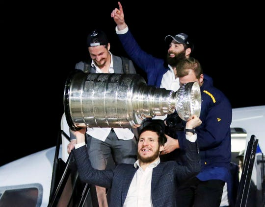St. Louis Blues player Alexander Steen hoists the Stanley Cup as the Blues arrive at the airport in St. Louis early Thursday.