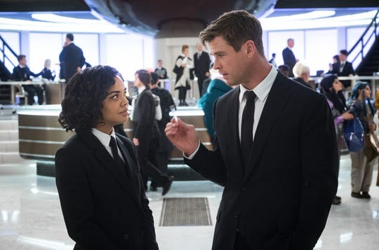 Agent M (Tessa Thompson) and Agent H (Chris Hemsworth) talk in the lobby of MIB London. Yes, he's man-splaining.