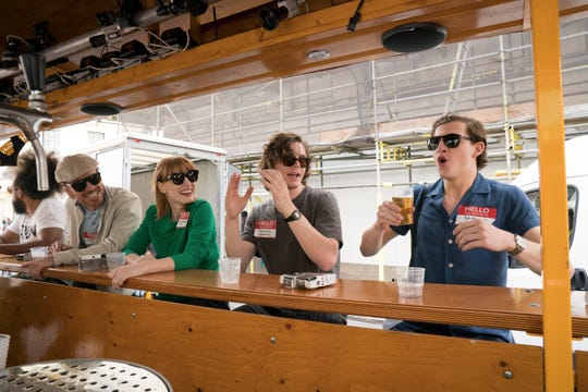 "Tye Sheridan, right, enjoys a drink as his fellow ""Dark Phoenix"" stars Evan Peters, second from right, Jessica Chastain and Michael Fassbender watch during a double-decker bus tour that is part of a London visit for CBS' 'The Late Late Show.'"
