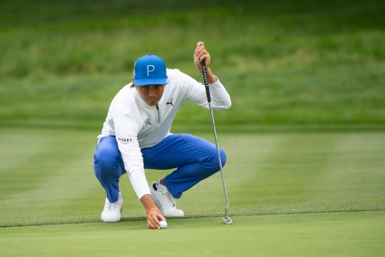 Rickie Fowler lines up his putt at the second green during the first round.