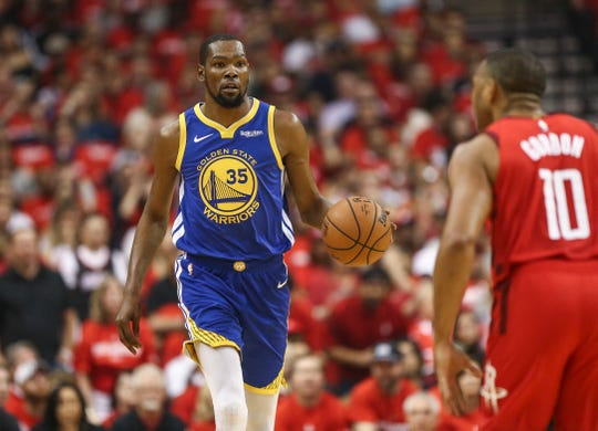 Golden State Warriors forward Kevin Durant dribbles the ball as Houston Rockets guard Eric Gordon defends.