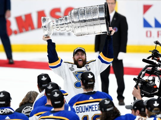 St. Louis Blues defenseman Alex Pietrangelo (27) holds the Stanley Cup in front of his team after the Blues defeated the Boston Bruins in Game 7.