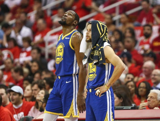 Golden State Warriors forward Kevin Durant and guard Stephen Curry look on.